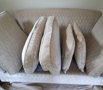 Showing how the cushions should be stacked on a sofa when cleaning has been completed and they will be left to dry