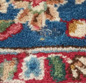 A Persian wool rug with damage caused by carpet moth