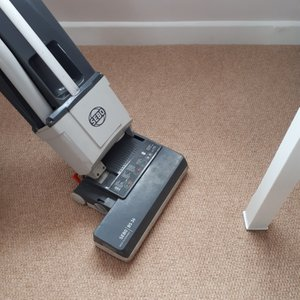 An industrial upright vacuum cleaner cleaning a carpet prior to wet cleaning