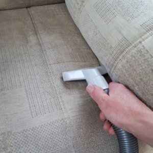 Using a hand tool to dry vacuum an armchair before cleaning