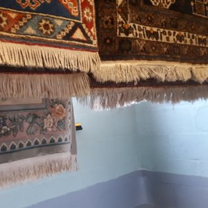 A couple of rugs hung up on a drying rack to allow them to dry out fully before treating the fringes